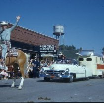 Image of Oak Lawn Round-Up Parade, 1954 - This is a photograph of the 1954 Oak Lawn Round-Up. It features the Round-Up parade moving westbound on 95th Street. Behrends Hardware store located at 5300 W. 95th Street, the Oak Lawn water tower located at 9437 S. Cook, and a sign for Sinclair Gasoline at the Safeway Motor Sales and Service station located at 5252 W. 95th can be seen in the background.