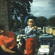 Image of Oak Lawn Round-Up Parade, 1954 - This is a photograph of the 1954 Oak Lawn Round-Up. It features a woman and a little girl dressed in western clothing watching the Round-Up parade from a high vantage point, possibly the roof of a business along 95th Street. The girl seems to be getting ready to load the cap gun at her feet. Another child in western clothing holding a toy gun and the Oak Lawn Public Library can be seen in the background.