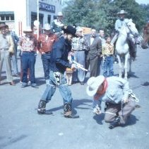 Image of 1954 Oak Lawn Round-Up - This is a photograph of the 1954 Oak Lawn Round-Up. It features one of the mock events staged during Round-Up in which a bandit in a black hat seems to be overcoming one of the good guys, possibly the sheriff as indicated by the white hat as bystanders, some in costume and on horseback and some not, look on near what is believed to be the Safeway Motor Sales and Service station located at 5252 W. 95th Street.