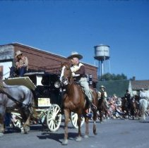 Image of Oak Lawn Round-Up Parade, 1954 - This is a photograph of the 1954 Oak Lawn Round-Up. It features the Round-Up parade moving westbound on 95th Street past Behrends Hardware store located at 5300 W. 95th Street. The Oak Lawn water tower located at 9437 S. Cook can be seen in the background.