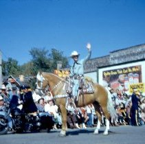Image of 1954 Oak Lawn Round-Up - This is a photograph of the 1954 Oak Lawn Round-Up. It features a rider on horseback in the Round-Up parade moving westbound on 95th Street past Behrends Hardware store located at 5300 W. 95th Street. A police officer on motorcycle can also be seen moving along with the parade.