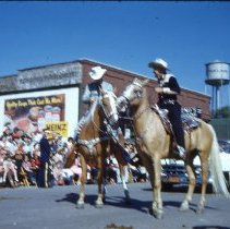 Image of Oak Lawn Round-Up Parade, 1954 - This is a photograph of the 1954 Oak Lawn Round-Up. It features two riders on horseback in the Round-Up parade moving westbound on 95th Street past Behrends Hardware store located at 5300 W. 95th Street. The Oak Lawn water tower located at 9437 S. Cook can be seen in the background.