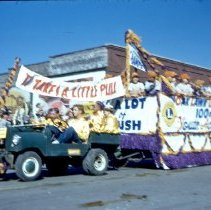 Image of 1954 Oak Lawn Round-Up - This is a photograph of the 1954 Oak Lawn Round-Up. It features a baseball team on a Lions float in the Round-Up parade as it moves westbound on 95th Street past Behrends Hardware store located at 5300 W. 95th Street. The Oak Lawn water tower located at 9437 S. Cook can be seen in the background.