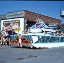 Image of 1954 Oak Lawn Round-Up - This is a photograph of the 1954 Oak Lawn Round-Up. It features a float sponsored by the Oak Lawn Chamber of Commerce in the Round-Up parade as it moves westbound on 95th Street past Behrends Hardware store located at 5300 W. 95th Street. The Oak Lawn water tower located at 9437 S. Cook can be seen in the background.