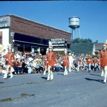 Image of 1954 Oak Lawn Round-Up - This is a photograph of the 1954 Oak Lawn Round-Up. It features a marching band performing in the Round-Up parade as it moves westbound on 95th Street. Behrends Hardware store located at 5300 W. 95th Street and the Oak Lawn water tower located at 9437 S. Cook, can be seen in the background.