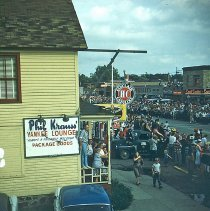 Image of 1954 Oak Lawn Round-Up - This is a photograph of the 1954 Oak Lawn Round-Up. It features a view of people watching the Round-Up parade from the porch of Phil Krauss' Yankee Lounge located at 5256 W. 95th Street. A Sinclair Gasoline sign at the Safeway Motor Sales & Service located at 5252 W. 95th Street is visible in the middle of the picture. In the background, signs for Hensley's Store located at 5217 W. 95th Street and Cupid Candies located at 5239 W. 95th Street are also visible.