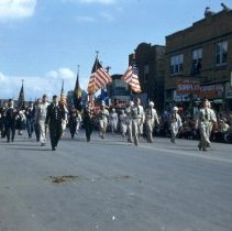 Image of 1954 Oak Lawn Round-Up - This is a photograph of the 1954 Oak Lawn Round-Up. It features an American Legion unit marching in the Round-Up parade. In the background, signs for Cupid Candies located at 5239 W. 95th Street, the S & S Surplus Store located at 5253 W. 95th Street, and are the Oak Lawn Book Shop are also visible. People can be seen watching the parade from the rooftops and windows of the buildings.