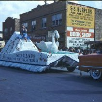 Image of 1954 Oak Lawn Round-Up - This is a photograph of the 1954 Oak Lawn Round-Up. It features a float from Smith Cleaners located at 5000 W, 95th Street in the Round-Up parade. In the background, signs for Cupid Candies located at 5239 W. 95th Street, the S & S Surplus Store located at 5253 W. 95th Street, and are the Oak Lawn Book Shop are also visible. People can be seen watching the parade from the rooftops and windows of the buildings.