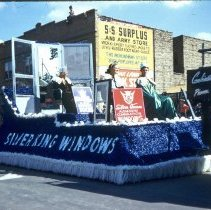 Image of 1954 Oak Lawn Round-Up - This is a photograph of the 1954 Oak Lawn Round-Up. It features a float from Silver King Windows in the Round-Up parade. In the background, the sign for Cupid Candies located at 5239 W. 95th Street is partially visible in the background. The S & S Surplus Store located at 5253 W. 95th Street, and are the Oak Lawn Book Shop are also partially visible. People can be seen watching the parade from the rooftops and windows of the buildings.