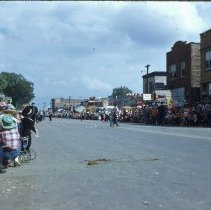 Image of 1954 Oak Lawn Round-Up - This is a photograph of the 1954 Oak Lawn Round-Up. It features a view of people lining 95th Street during the Round-Up parade. On the left, a sign for Sinclair Gasoline at the Safeway Motor Sales & Service located at 5252 W. 95th Street can be seen. On the right, Hensley's Store located at 5217 W. 95th Street, Cupid Candies located at 5239 W. 95th Street, Margie's Candies and the S & S Surplus Store located at 5253 W. 95th Street are visible. People can be seen watching the parade from the rooftops and windows of the buildings.