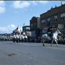 Image of 1954 Oak Lawn Round-Up - This is a photograph of the 1954 Oak Lawn Round-Up. It features a rider on horseback leading a marching band during the Round-Up parade. In the background on the right, Hensley's Store located at 5217 W. 95th Street, Cupid Candies located at 5239 W. 95th Street, Margie's Candies, the S & S Surplus Store and the Oak Lawn Book Shop located in the 5253 W. 95th Street building are visible. People can be seen watching the parade from the rooftops and windows of the buildings.