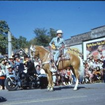 Image of 1954 Oak Lawn Round-Up - This is a photograph of the 1954 Oak Lawn Round-Up. It features a rider on horseback in the Round-Up parade moving westbound on 95th Street. The Behrends residence located at 9446 S. Raymond can be seen in the backgound. Behrends Hardware store located at 5300 W. 95th Street is the building in the right of the frame. A police officer on motorcycle can also be seen moving along with the parade.