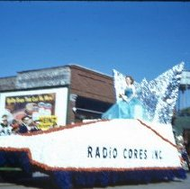 Image of Oak Lawn Round-Up Parade, 1954 - This is a photograph of the Oak Lawn Round-Up Parade. It features a float representing Radio Cores, Inc. located at 9540 S. Tulley in the Round-Up parade as it moves westbound on 95th Street. Behrends Hardware store located at 5300 W. 95th Street, a horse drawn carriage, and the Oak Lawn water tower located at 9437 S. Cook, can be seen in the background.
