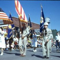 Image of Oak Lawn Round-Up Parade, 1954 - This is a photograph of the 1954 Oak Lawn Round-Up. It features an American Legion unit marching in the Round-Up parade. In the background, Behrends Hardware Store located at 5300 W. 95th Street and the Oak Lawn water tower located at  9437 S. Cook can be seen.