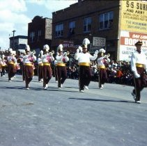 Image of 1954 Oak Lawn Round-Up - This is a photograph of the 1954 Oak Lawn Round-Up. It features a marching band in the Round-Up parade. In the background on the right, Margie's Candies, the S & S Surplus Store and the Oak Lawn Book Shop located in the 5253 W. 95th Street building are visible. People can be seen watching the parade from the rooftops and windows of the buildings.