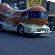 Image of Oak Lawn Round-Up Parade, 1954 - This is a photograph of the 1954 Oak Lawn Round-Up. It features the Oscar Mayer Weinermobile in the Round-Up parade. A horse and rider can been seen behind the vehicle. People can be seen watching the parade from the rooftops and windows of the buildings.