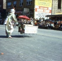 Image of 1954 Oak Lawn Round-Up - This is a photograph of the 1954 Oak Lawn Round-Up. It features a clown pushing a cart in the Oak Lawn Round-Up parade. On the right, Cupid Candies located at 5239 W. 95th Street, the S & S Surplus Store and the Oak Lawn Book Shop located at 5253 W. 95th Street are visible. People can be seen watching the parade from the windows of the building.