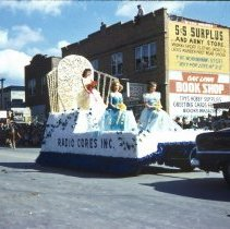 Image of 1954 Oak Lawn Round-Up - This is a photograph of the 1954 Oak Lawn Round-Up. It features a float representing Radio Cores, Inc. located at 9540 S. Tulley in the Round-Up parade as it moves westbound on 95th Street. On the right, Cupid Candies located at 5239 W. 95th Street, the S & S Surplus Store and the Oak Lawn Book Shop located at 5253 W. 95th Street are visible. People can be seen watching the parade from the windows and the rooftop of the buildings.