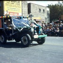 Image of Oak Lawn Round-Up Parade, 1954 - This is a photograph of the 1954 Oak Lawn Round-Up. It features an unidentified woman holding a dog and two other people in a Jeep in the Round-Up parade. The S & S Surplus Store and the Oak Lawn Book Shop located at 5253 W. 95th Street can be seen in the background. People can be seen watching the parade from the windows and the rooftop of the buildings.