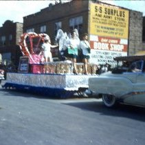 Image of Oak Lawn Round-Up Parade, 1954 - This is a photograph of the 1954 Oak Lawn Round-Up. It features an unidentified float in the Round-Up parade as it moves westbound on 95th Street. In the background right, Cupid Candies located at 5239 W. 95th Street, the S & S Surplus Store and the Oak Lawn Book Shop located at 5253 W. 95th Street are visible. People can be seen watching the parade from the windows and the rooftop of the buildings.