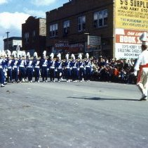 Image of 1954 Oak Lawn Round-Up - This is a photograph of the 1954 Oak Lawn Round-Up. It features a marching band in the Round-Up parade. Margie's Candies, the S & S Surplus Store and the Oak Lawn Book Shop located in the 5253 W. 95th Street building are visible on the right. People can be seen watching the parade from the windows of the buildings.