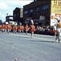Image of 1954 Oak Lawn Round-Up - This is a photograph of the 1954 Oak Lawn Round-Up. It features a marching band in the Round-Up parade. In the right background, Henseley's Store located at 5217 W. 95th Street, Cupid Candies, located at 5239 W. 95th Street, Margie's Candies, the S & S Surplus Store and the Oak Lawn Book Shop located in the 5253 W. 95th Street building are visible. People can be seen watching the parade from the windows of the buildings.