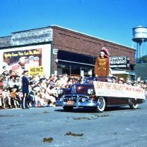 Image of 1954 Oak Lawn Round-Up - This is a photograph of the 1954 Oak Lawn Round-Up. It features a car carrying the world's tallest man in America (Donald A. Koehler) dressed as an Indian in the Round-Up parade as it moves westbound on 95th Street. Behrends Hardware store located at 5300 W. 95th Street, a horse drawn carriage, and the Oak Lawn water tower located at 9437 S. Cook, can be seen in the background.
