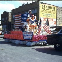 Image of 1954 Oak Lawn Round-Up - This is a photograph of the 1954 Oak Lawn Round-Up. It features a float representing Albert Brandt as the Committeeman of the Worth Township Regular Democratic Club in the Round-Up parade as it moves westbound on 95th Street. In the background right, Cupid Candies located at 5239 W. 95th Street and the 5253 W. 95th Street building are visible. People can be seen watching the parade from the windows and the rooftop of the buildings.