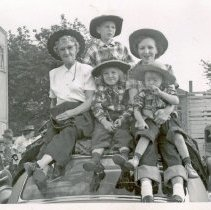 Image of Oak Lawn Round-Up, 1954 - This is a photograph of the 1954 Oak Lawn Round-Up. It features two women and three children in western wear sitting on the roof of a car possibly watching the Round-Up parade. More people sitting on cars can be seen in the background.