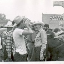 Image of 1954 Oak Lawn Round-Up - This is a photograph of the 1954 Oak Lawn Round-Up. It features a crowd outside of a local tavern in the 5200 block of 95th Street. One man is drinking something from what appears to be an enamel pot. In the left background, gas pumps at Safeway Motor Sales and Service located at 5252 W. 95th are visible. The building on the left in the distance is Nick's Tap located at 5220 W. 95th Street. A sign for Wolf's Bakery located at 5263 W. 95th Street can be seen in the background on the right and a mule is visible in the right foreground.