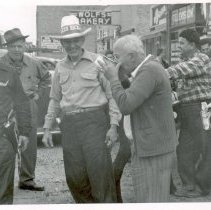 Image of Oak Lawn Round-Up, 1954 - This is a photograph of the 1954 Oak Lawn Round-Up. It features a crowd dressed in western wear outside of a local tavern in the 5200 block of 95th Street. One man is drinking something from what appears to be an enamel pot as others look on. A sign for Wolf's Bakery located at 5263 W. 95th Street can be seen in the background on the right and a mule is visible in the right foreground. The store front of the Lincoln Meat Market located at 5967 W. 95th Street is partially visible in the far right of the picture.