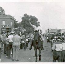 Image of 1954 Oak Lawn Round-Up - This is a photograph of the 1954 Oak Lawn Round-Up. It features a crowd standing along 95th Street as riders on horseback pass by during the Round-Up parade. On the right, the Sinclair Gasoline sign at Safeway Motor Sales and Service located at 5252 W. 95th Street is visible as is Nick's Tap Room located at 5220 W. 95th Street and McKay's Ladies Wear and Jewelry located at 5216 W. 95th Street. In the far background on the right, the Coca Cola sign on the Brandt building located at 5137 W. 95th Street is visible. A ferris wheel and people sitting on the roof of a building as well as a sign for Paulin Cleaners are also seen on the right.