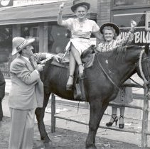 Image of 1954 Oak Lawn Round-Up - This is a photograph of the 1954 Oak Lawn Round-Up. It features an unidentified man in an Oak Lawn Round-Up hat pointing a gun at two unidentified women, one sitting astride a horse, both wearing cowboy hats, outside a drinking establishment located in the 5200 block of 95th Street. Another unidentified woman and man on either side of the group are also pictured.