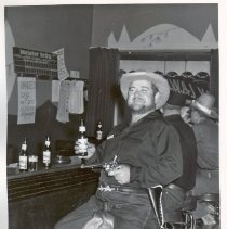 Image of 1954 Oak Lawn Round-Up - This is a photograph of the 1954 Oak Lawn Round-Up. It features an unidentified man in western wear sitting on a saddle on a bar stool in an unidentified tavern as he holds a bottle of beer on one hand and his revolver in the other. A Wanted Poster for Fearless Freddy is posted behind the bar. Two other customers, also in western wear, can be seen in the background.