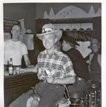 Image of 1954 Oak Lawn Round-Up - This is a photograph of the 1954 Oak Lawn Round-Up. It features an unidentified man in Oak Lawn Round-Up cowboy hat sitting on a saddle on a bar stool in an unidentified tavern as he holds a glass of beer on one hand and his revolver in the other. An unidentified man tends the bar and two other customers, also in western wear, can be seen in the background.