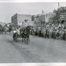 Image of 1954 Oak Lawn Round-Up - This is a photograph of the 1954 Oak Lawn Round-Up. It features crowds of people, many dressed in Western wear, lining both sides of 95th Street to watch the Round-Up parade. A horse drawn wagon and a group of people on horseback are passing in the parade.  A sign for Wolf's Bakery located at 5263 W. 95th Street can be seen in the background on the right as well as the Lincoln Meat Market located at 5967 W. 95th Street and the Ratajik Pharmacy located at 5269 W. 95th Street.