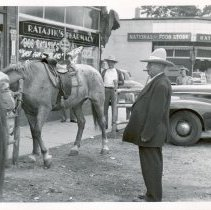 Image of Oak Lawn Round-Up, 1954 - This is a photograph of the 1954 Oak Lawn Round-Up. It features several men, some in Western wear, with horses outside of the Lincoln Meat Market located at 5967 W. 95th Street and the Ratajik Pharmacy located at 5269 W. 95th Street. The National Food Store, seen in the background, was located at approximately the corner of 95th Street and 53rd Avenue.