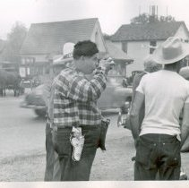 Image of 1954 Oak Lawn Round-Up - This is a photograph of the 1954 Oak Lawn Round-Up. It features a group of men dressed in western wear approximately the 5200 block of 95th Street. One man is drinking something from what appears to be an enamel pot. A car can be seen going eastbound on 95th Street. A horse and carriage is seen across the street. The base structure of the Oak Lawn water tower can be seen behind the house in the background of the picture. The corner of the building housing Nick's Tap Room located at 5220 W. 95th Street can be seen in the far right background.