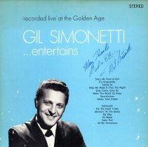 Image of Gil Simonetti...Entertains - This item is a 33 1/3 RPM record featuring tracks from Gil Simonetti. This album was recorded at the Golden Age Restaurant located at 4545 West 95th Street in Oak Lawn. The cover is blue in color and features an image of Gil Simonetti.