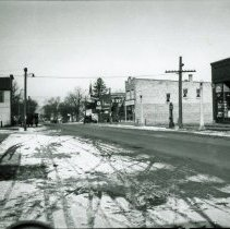 Image of 95th Street Looking West From 53rd Avenue - This is a photograph of 95th Street looking west from 53rd Avenue. Larsen's Hall is visible on the left while businesses such as Behrend's Hardware and the Oak Lawn Trust and Savings Bank are on the right. The steeple of St. Gerald Church can be seen in the distance.