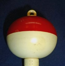 Image of Doozee Fishing Bobber - This item is a fishing bobber produced by the Doozee Corporation located at 10207 Ridgeland Avenue in Oak Lawn.  The bobber is red and white in color.