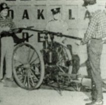 Image of Manual Fire Pump - This is a slide featuring a group of Oak Lawn Fire Department personnel (left to right) Chief Elmore Harker, Ken Shoot, Bill Fett, Jim Bennett, and Charlie Boecher examining a 1888 manual pumper on loan from the Dolton Fire Department for Oak Lawn Round-Up days parade. Four men were needed to haul the pump to a fire.