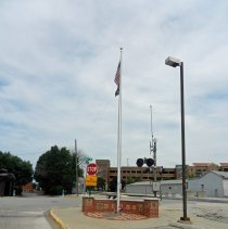 Image of Veterans of Foreign Wars Memorial and Flagpole - This is a photograph of the Veterans of Foreign Wars Memorial and Flagpole located on the southwest corner of 52nd Avenue and Yourell Drive. The memorial was established as an Eagle Scout project by Justin Aubin. Visible in the background is the railroad crossing on 52nd Avenue. The former Beatty Lumber Company buildings can be seen across the tracks to the southeast. In the distance, the Oak Lawn Metra Station parking structure located at 9525 Tulley Avenue is visible.