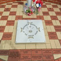 Image of Veterans of Foreign Wars Memorial and Flagpole - This is a photograph of the Veterans of Foreign Wars Memorial and Flagpole located on the southwest corner of 52nd Avenue and Yourell Drive. The memorial was established as an Eagle Scout project by Justin Aubin. The photograph features a view of the blocks on the floor of the memorial were donated and dedicated in memory of different service personnel.