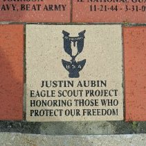 Image of Veterans of Foreign Wars Memorial and Flagpole - This is a photograph of the Veterans of Foreign Wars Memorial and Flagpole located on the southwest corner of 52nd Avenue and Yourell Drive. It features a view of a block on the floor of the memorial indicating that the memorial was an Eagle Scout Project by Justin Aubin.