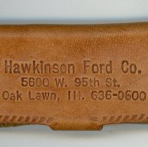 Image of Hawkinson Ford Key Case - This item is a key case distributed by Hawkinson Ford located at 5600 West 95th Street in Oak Lawn. It is tan in color and features contact information.
