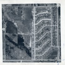 Image of Aerial Photograph of Oak Lawn - This item is an aerial photograph of Oak Lawn taken around 1955. 111th Street is visible on the bottom and Crawford (Pulaski) Road can be seen on the right. Rows of new homes stretch across the length of the photo.
