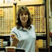 Image of A Weekend in the Life of Oak Lawn - This is a photograph of everyday life in Oak Lawn during 1987. It features An employee believed to be Pam Sanders holding a roll of film at the Oak Lawn Camera Shop located at 4949 W. 95th Street. A wall containing many boxes of different types of film can be seen behind her.