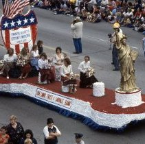Image of 1982 Oak Lawn Centennial Parade - This item is a slide of the 1982 Oak Lawn Centennial Parade. This is a view of the Oak Lawn Trust and Savings Bank float in the Centennial parade moving down 95th Street. Crowds of spectators can be seen on lining both sides of 95th Street to view the parade. This event celebrated the one hundredth anniversary of Oak Lawn's official survey and the completion of the railroad.