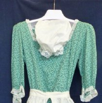 "Image of Bicentennial Celebration Costume - This item is a costume created for the 1976 Bicentennial Celebration. It is meant to represent the type of dress worn during the American Colonial Period and is green in color with a white hat and apron. That year Oak Lawn held a ""67 in 76"" event that commemorated the Village's anniversary as well."